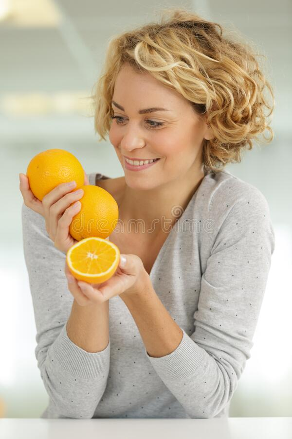 Beautiful blonde woman with orange smiling royalty free stock photography