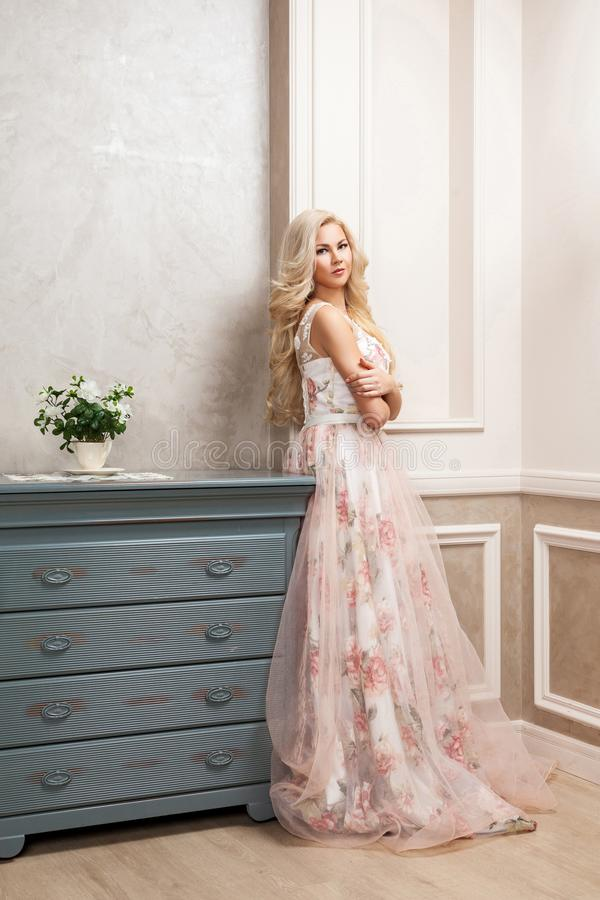 Beautiful blonde woman in pastel floral long puffy dress with makeup and long curly hairstyle leaning and posing near dresser at royalty free stock image