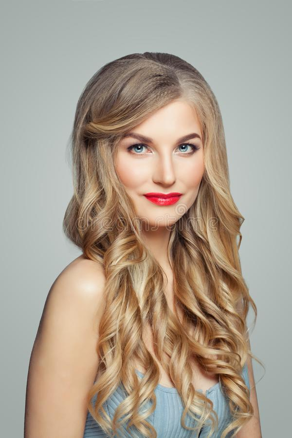 Beautiful blonde woman portrait. Elegant female model with long healthy curly hair and red lips makeup stock photo