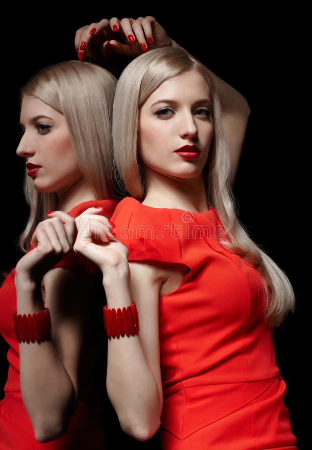 Beautiful blonde woman. Portrait of young beautiful long-haired blonde woman in red dress and bracelet at mirror stock images