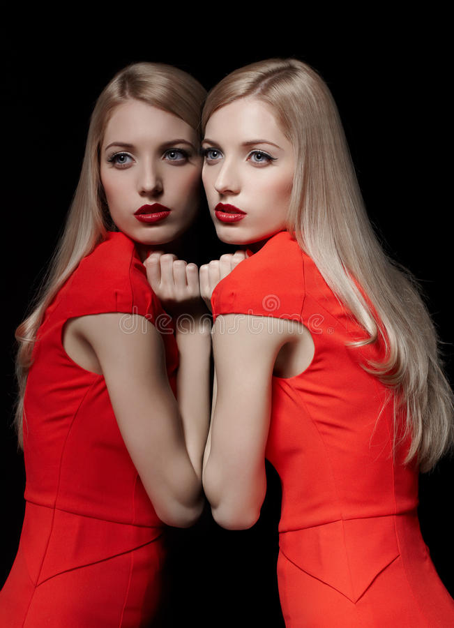 Beautiful blonde woman. Portrait of young beautiful long-haired blonde woman in red dress leaning at her reflection at mirror stock photo