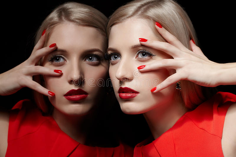 Beautiful blonde woman. Portrait of young beautiful long-haired blonde woman in red dress leaning at mirror and touching her face with red manicured fingers stock photos