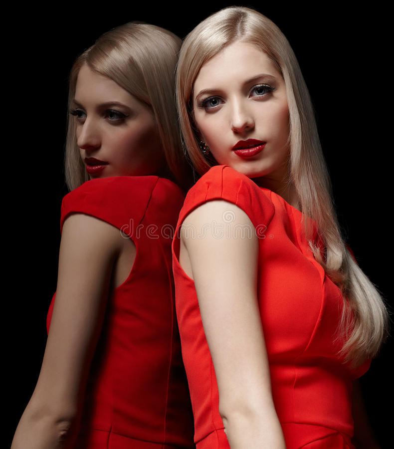 Beautiful blonde woman. Portrait of young beautiful long-haired blonde woman in red dress at mirror royalty free stock images