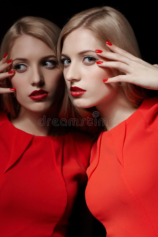 Beautiful blonde woman. Portrait of young beautiful long-haired blonde woman in red dress standing close to mirror and touching her face with red manicured royalty free stock photography