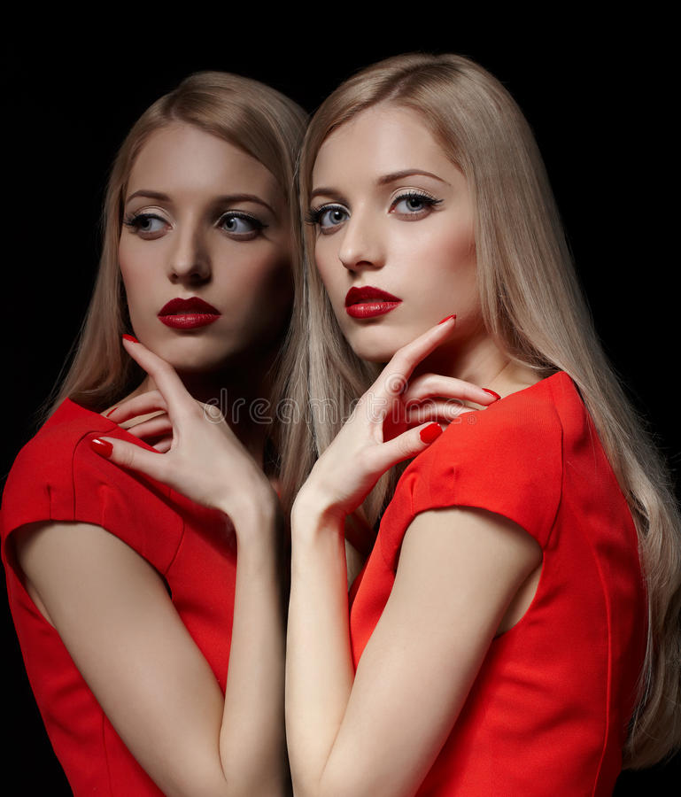 Beautiful blonde woman. Portrait of young beautiful long-haired blonde woman in red dress touching her face with manicured fingers at mirror stock photography