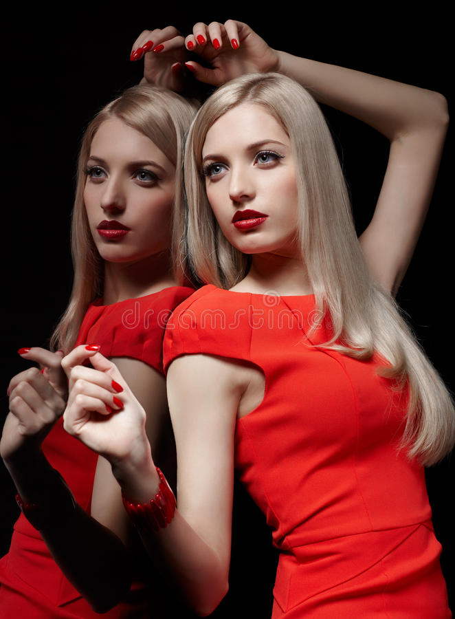 Beautiful blonde woman. Portrait of young beautiful blonde woman in red dress lean against the mirror stock images