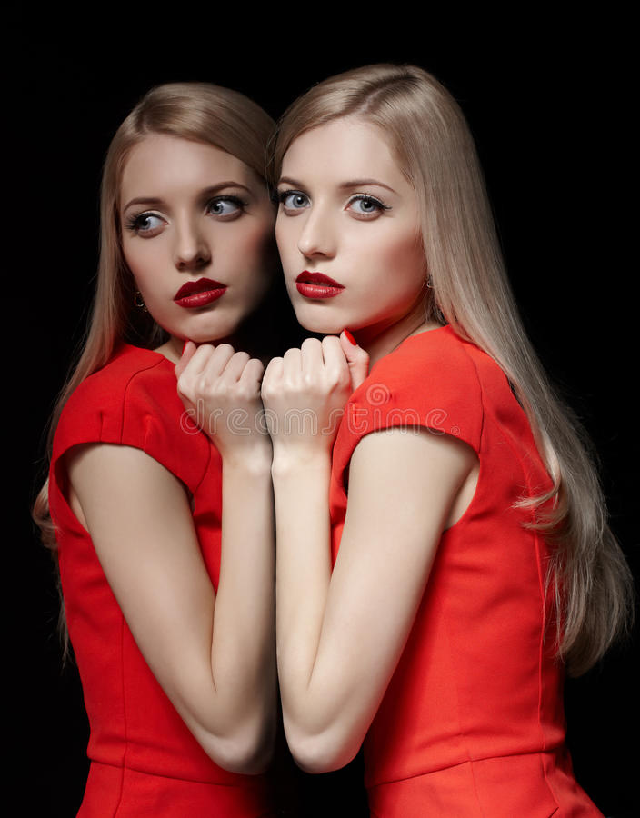 Beautiful blonde woman. Portrait of young beautiful blonde woman in red dress leaning at her reflection at mirror royalty free stock image