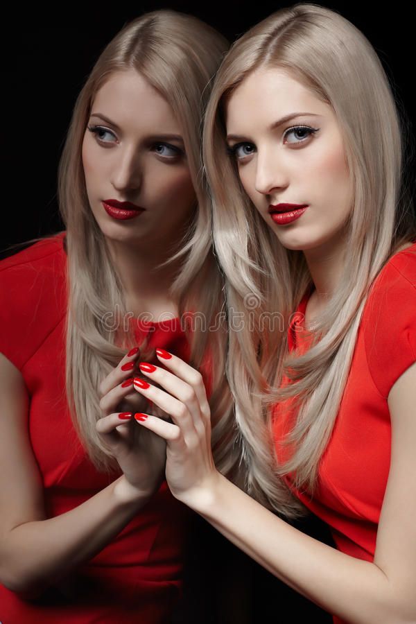 Beautiful blonde woman. Portrait of young beautiful blonde woman in red dress at mirror touching her reflection with manicured fingers stock image