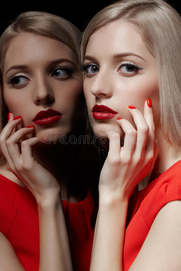 Beautiful blonde woman. Portrait of young beautiful blonde woman in red dress posing at mirror and touching her face with manicured fingers royalty free stock photography