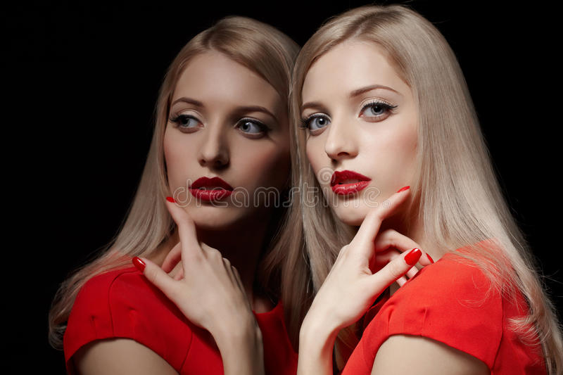 Beautiful blonde woman. Portrait of young beautiful blonde woman in red dress touching her cheek with manicured finger at mirror stock images