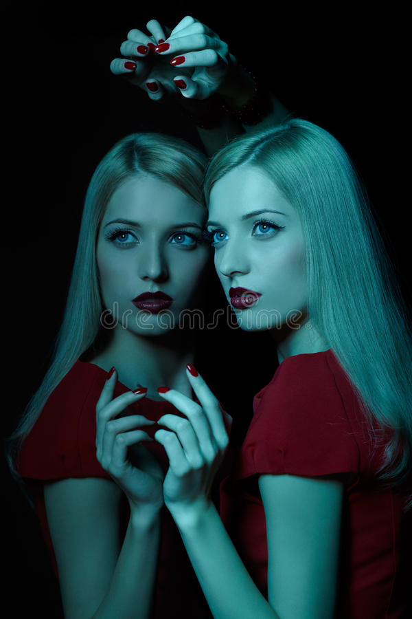 Beautiful blonde woman. Portrait of beautiful young blonde woman in teal light at mirror royalty free stock photo