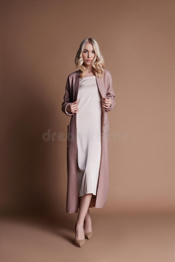 Beautiful blonde woman posing in a pink coat on a beige background. Fashion show clothing, woman with perfect figure, long hair royalty free stock photo
