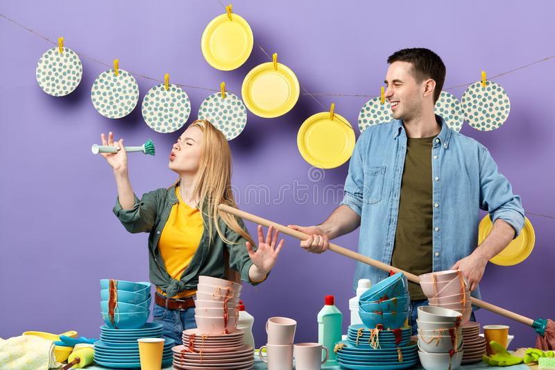 Beautiful blonde woman pretends to sing song with brush and smiling young stock photography