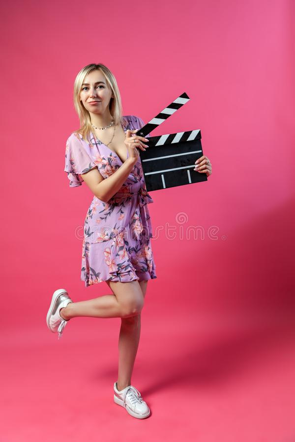 Beautiful blonde woman in a purple sundress holds an open clapperboard filmmaker in black with white stripes to start shooting a. Film and lifts one leg on pink royalty free stock photo