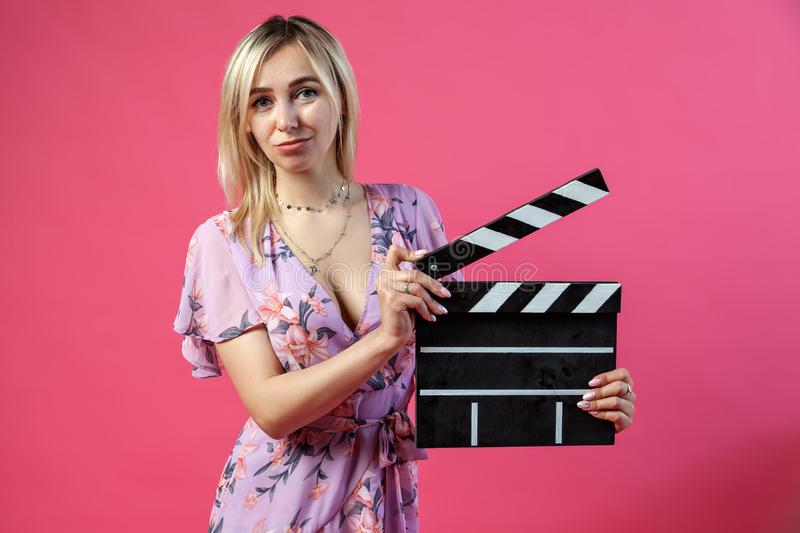 Beautiful blonde woman in a purple sundress holds an open clapperboard filmmaker in black with white stripes to start shooting a stock image