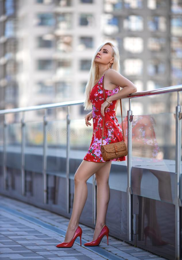Woman in red dress posing on the city square royalty free stock photography