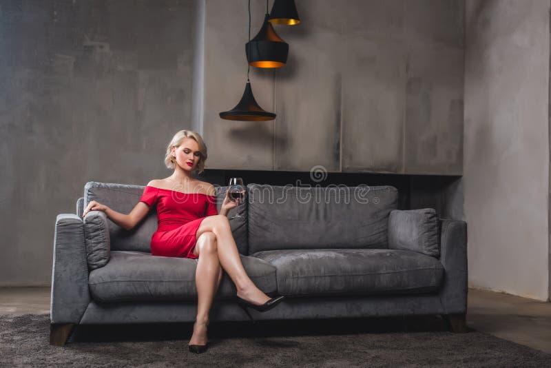 beautiful blonde woman in red dress sitting on sofa stock photo