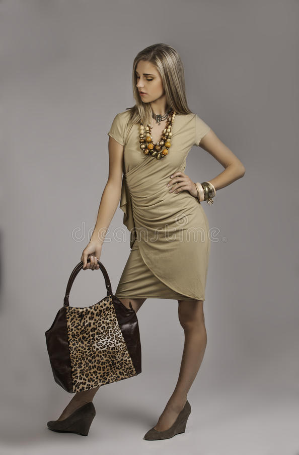 Beautiful blonde woman in safari chic outfit with animal print handbag stock photo