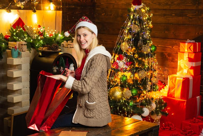 Beautiful blonde woman in Santa`s hat try to find her Christmas presents gifts. Christmas interior. Family winter royalty free stock photos