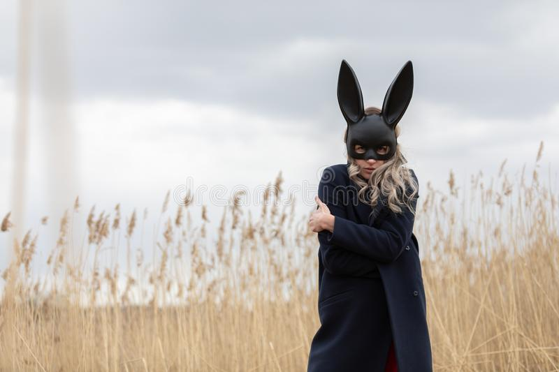 Beautiful blonde woman with scared face in black bunny mask. Posing outdoors. Monochrome image royalty free stock photos