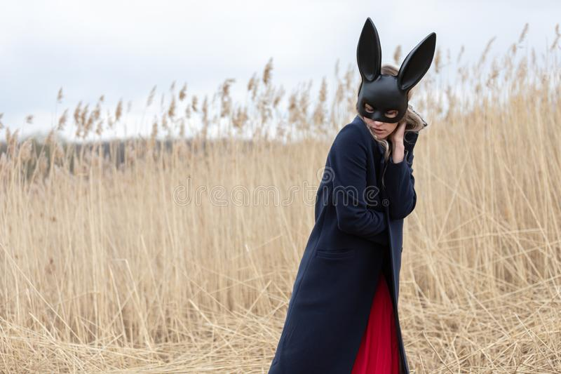 Beautiful blonde woman with scared face in black bunny mask. Posing outdoors. Monochrome image royalty free stock photo