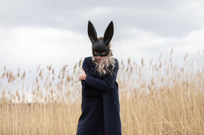 Beautiful blonde woman with scared face in black bunny mask. Posing outdoors. Monochrome image stock images