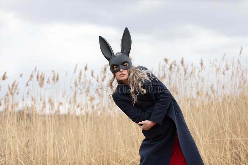 Beautiful blonde woman with scared face in black bunny mask. Posing outdoors. Monochrome image royalty free stock photography