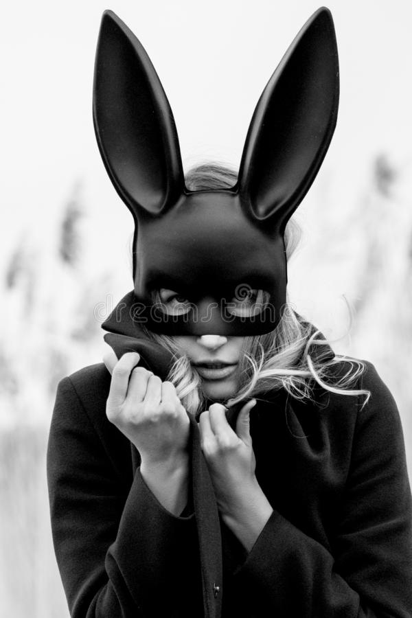 Beautiful blonde woman with scared face in black bunny mask. Posing outdoors. Monochrome image stock photo