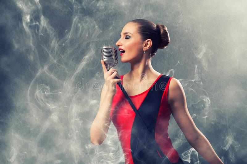 Beautiful blonde woman singer with a microphone. Eyes closed, around smoke stock photography