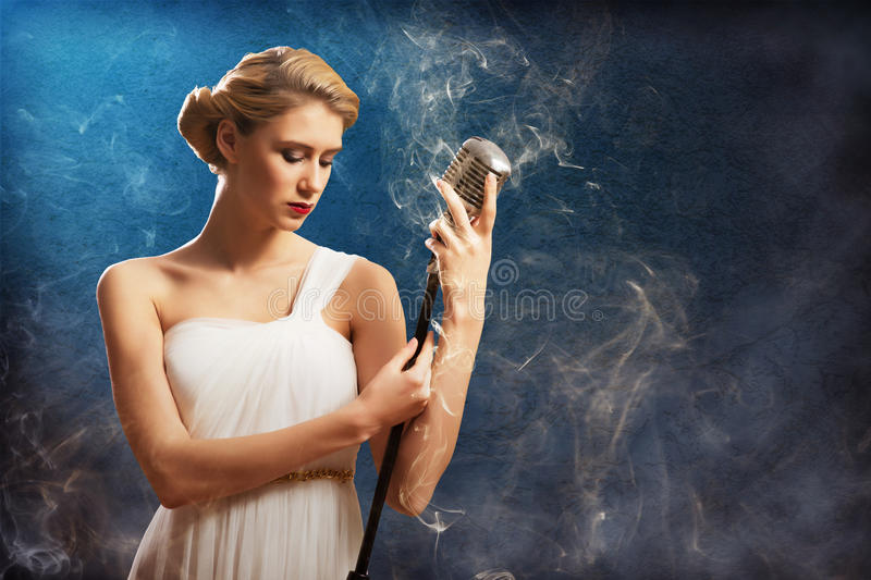 Beautiful blonde woman singer with a microphone. Eyes closed, around smoke stock photos