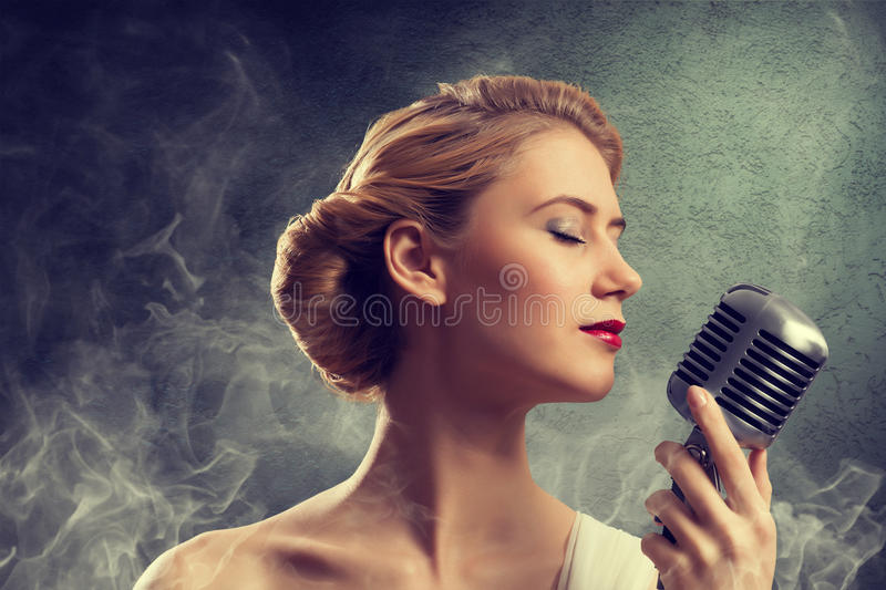 Beautiful blonde woman singer with a microphone. Eyes closed, around smoke royalty free stock image
