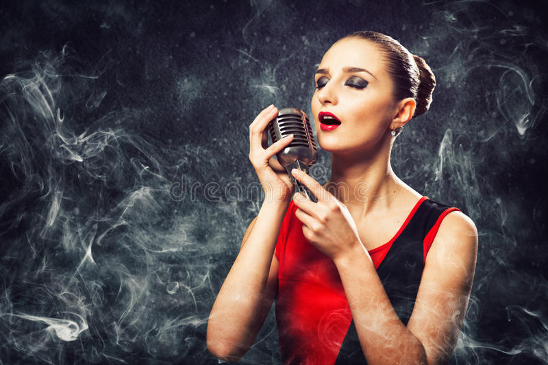 Beautiful blonde woman singer with a microphone. Eyes closed, around smoke stock images