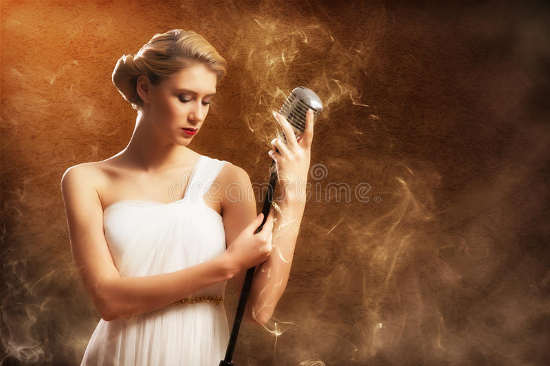 Beautiful blonde woman singer with a microphone. Eyes closed, around smoke royalty free stock photo