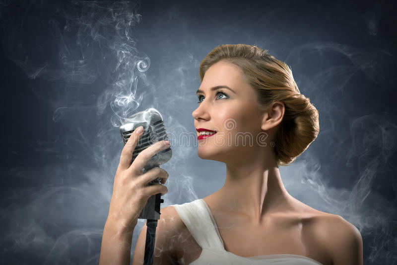 Beautiful blonde woman singer with a microphone. Eyes opened, around smoke stock images