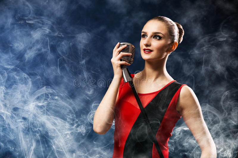 Beautiful blonde woman singer with a microphone. Eyes opened, around smoke royalty free stock images