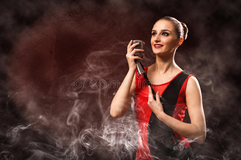 Beautiful blonde woman singer with a microphone. Eyes opened, around smoke royalty free stock photography