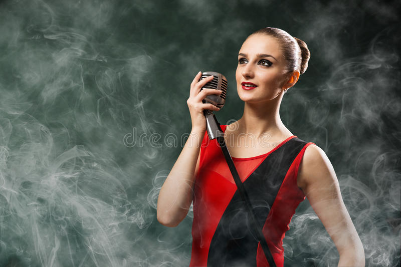 Beautiful blonde woman singer with a microphone. Eyes opened, around smoke stock image