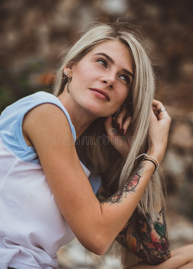 Beautiful blonde woman sitting on a stone embankment and reads book. Hands tattooed. modern, trendy, student. Closeup stock photos