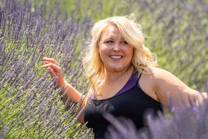 Beautiful blonde woman smiles and looks away as she sits in a field of lavender. Taken in Mt. Hood Oregon stock photos