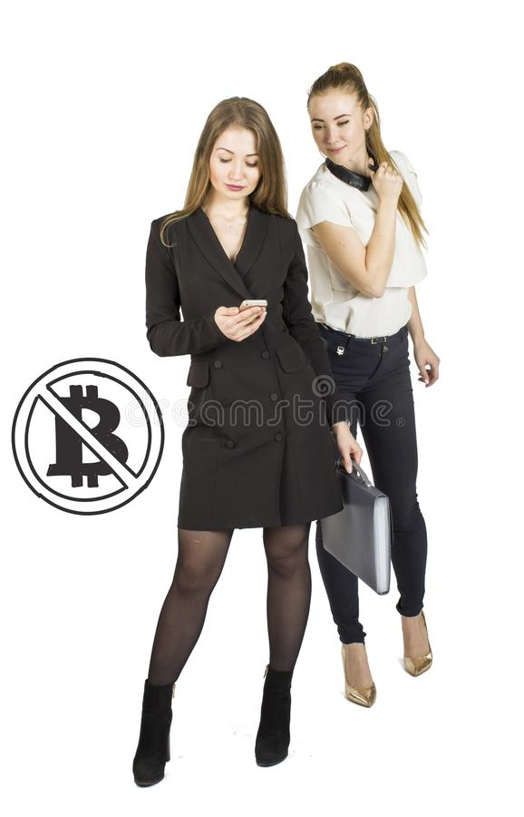 Beautiful women standing over white background with bitcoin sketches and talking. Virtual money concept. Cryptocurrency royalty free stock images
