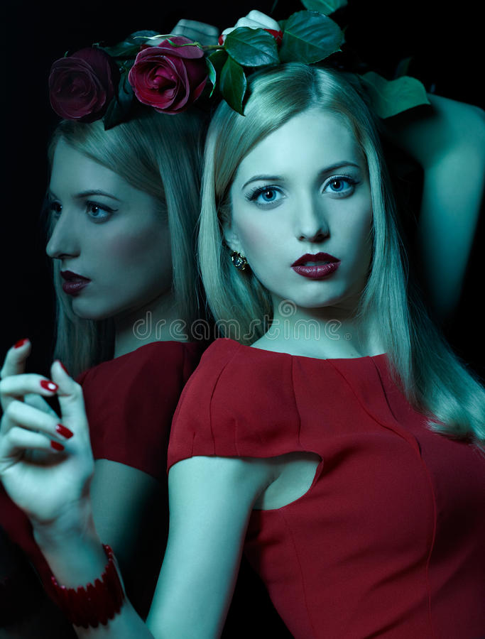 Beautiful blonde woman. Teal toned portrait of beautiful young blonde woman with red rose at mirror stock image