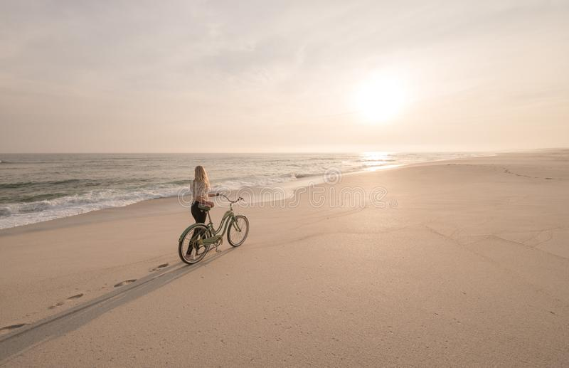 Beautiful blonde woman walking with her bicycle down a quiet beach at sunset. stock image