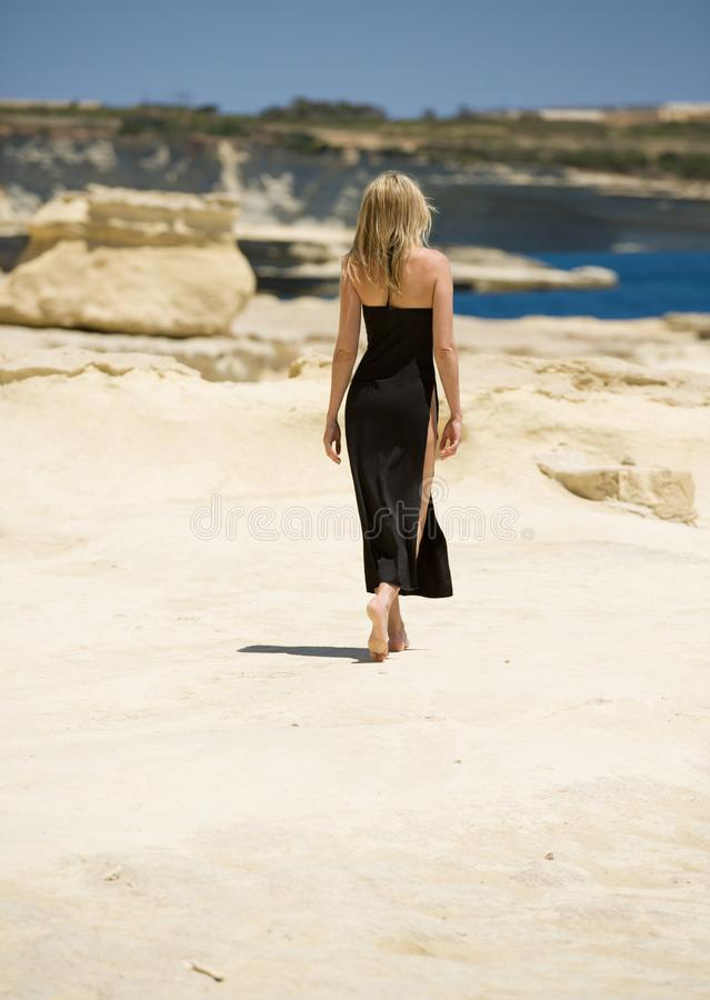 Beautiful blonde woman walks away bare foot, in sexy long dress at beach of Malta. Beautiful slim lady walks away in simple, elegant long dress at the beach royalty free stock images