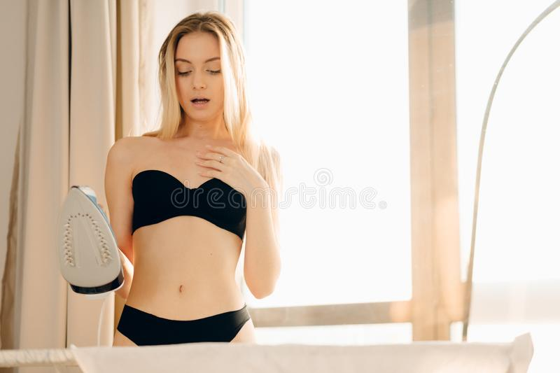 Beautiful blonde woman wearing lingerie preparing to offic irons her shirt. stock photos