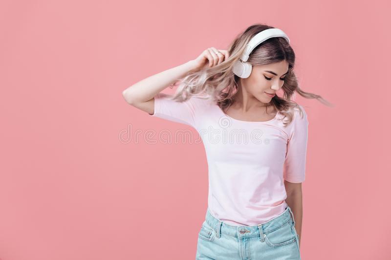 Beautiful blonde woman in white headphones listens to music royalty free stock photography