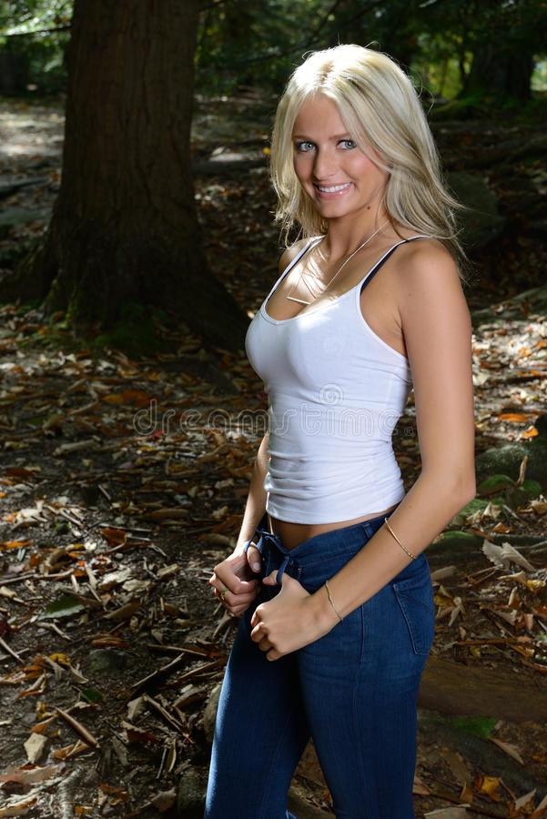 Beautiful Blonde Woman In White Tank And Jeans In Woods