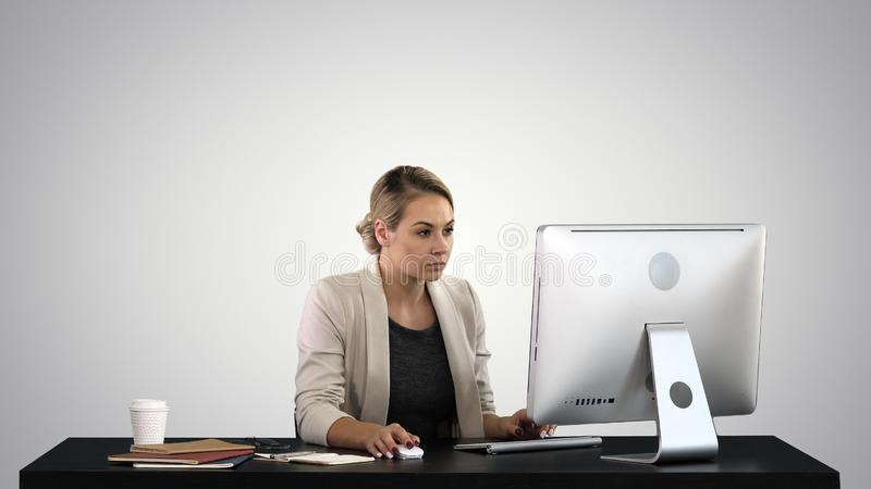 Beautiful blonde woman working on computer on gradient background. stock photo