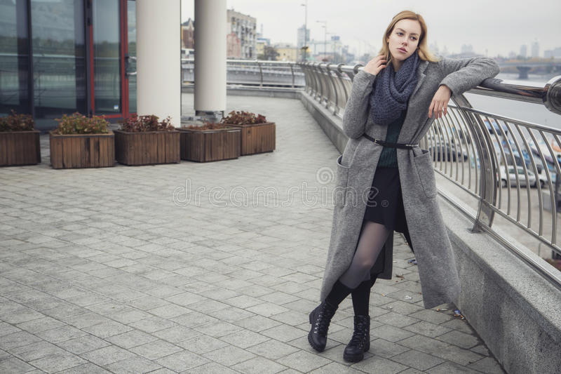 Beautiful blonde young caucasian woman in grey coat and scarf wa. Lking in european city on a cold rainy cloudy day, a bit sad and thoughtful royalty free stock images