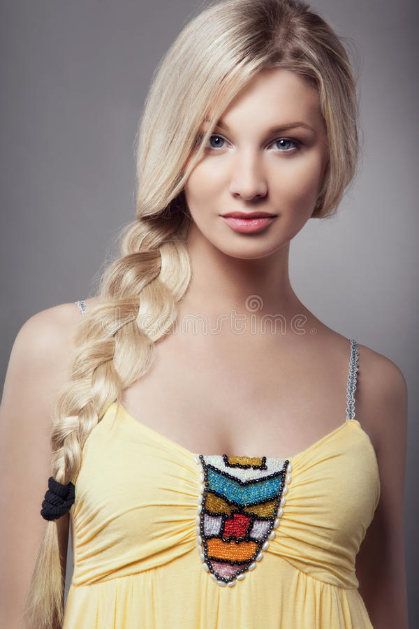 Blonde young woman with braid hairdo royalty free stock image