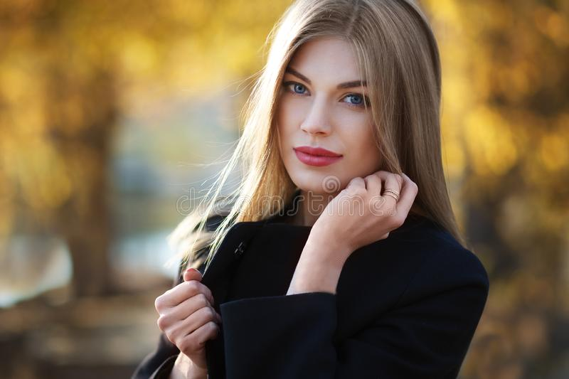 Beautiful blonde young woman in nice black coat. Posing on golden autumn background. Fashion Photo stock photo
